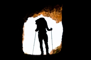 Excursionist getting out of a cave - Pasubio Mountain, Italy