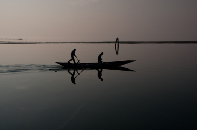 Paddlers in the lagoon - backlight - Italy