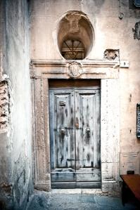 Wooden door in a blind street, Montepulciano (Siena) Italy